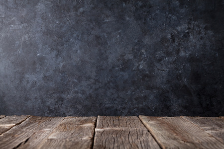 Old wooden table in front of black chalkboard wall for your text. View with copy space