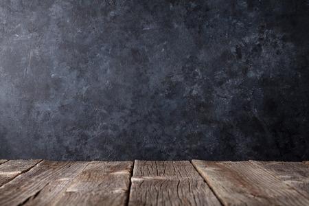 テキストの黒の黒板壁の前に古い木製のテーブル。コピー スペースを表示します。