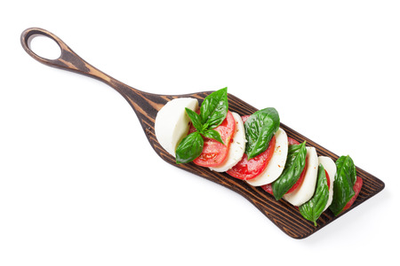 basil herb: Caprese salad. Mozzarella cheese, tomatoes and basil herb leaves on cutting board. Isolated on white background. Top view