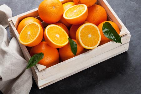 돌 테이블에 나무 상자에 신선한 오렌지 과일