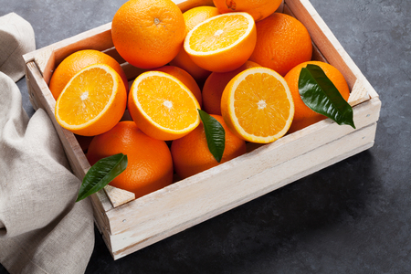 Fresh orange fruits in wooden box on stone table