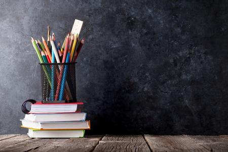 Suministra más de blocs de notas en frente del tablero de tiza. Volver al concepto de escuela con el espacio de la copia Foto de archivo