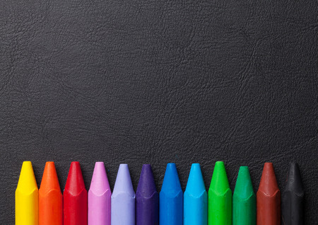 Colorful pencils over leather desk table. Top view with copy space Stock Photo