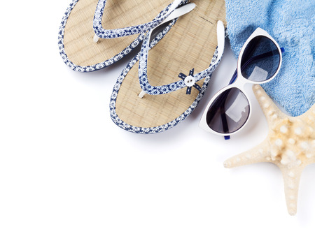Beach accessories. Flip flops, sunglasses and starfish. Isolated on white background. Top view with copy space