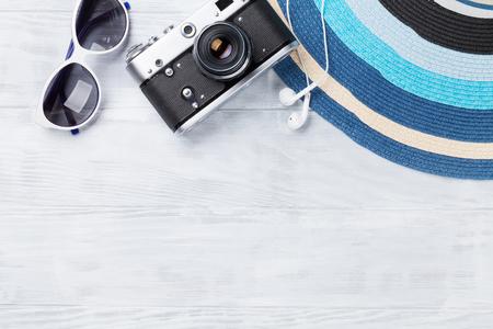 Strandtoebehoren. Camera, hoed en zonnebril op houten achtergrond. Bovenaanzicht met kopie ruimte