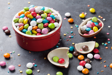 chocolate egg: Colorful candies and chocolate egg on stone background