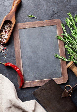 stone cutter: Herbs and spices cooking on stone table. Rosemary, pepper and salt. Top view with blackboard for your text Stock Photo