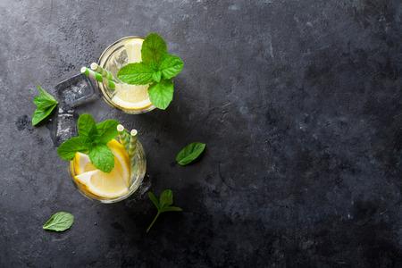 menta: Limonada con limón, menta y hielo sobre la mesa de piedra. Vista superior con espacio de copia