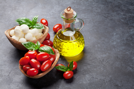 copyspace: Mozzarella cheese, tomatoes and basil herb leaves over stone table. View with copy space