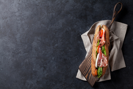 Ciabatta sandwich with romaine salad, prosciutto and mozzarella cheese over stone background. Top view with copy space Banco de Imagens