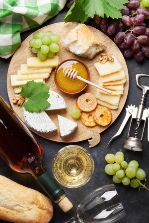 delicatessen: White wine, grape, cheese plate and honey over stone table. Top view