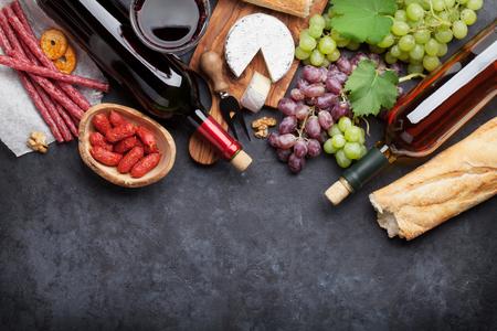 uvas: botellas de vino tinto y blanco, uva, queso y salchichas sobre la mesa de piedra. Vista superior con espacio de copia