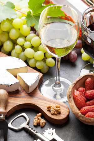 Red and white wine glasses, grape, cheese and sausages over stone table Stock Photo