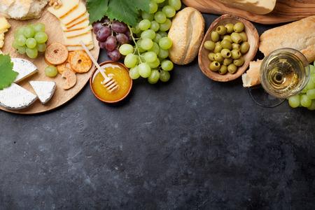 queso fresco blanco: Vino blanco, uva, pan, plato de queso y miel sobre la mesa de piedra. Vista superior con espacio de copia