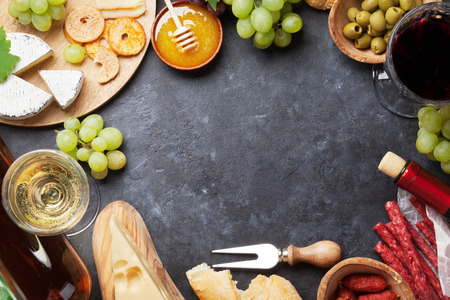 Red and white wine, grape, honey, cheese and sausages over stone table. Top view with copy space Stok Fotoğraf - 61469164