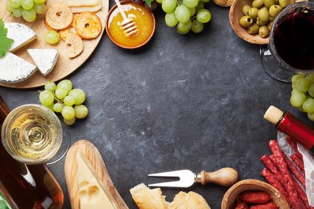 Rot- und Weißwein, Traube, Honig, Käse und Wurst über Steintisch. Draufsicht mit Kopie Raum