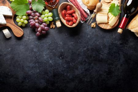 Rode en witte wijn flessen, druif, kaas en worst over stenen tafel. Bovenaanzicht met een kopie ruimte