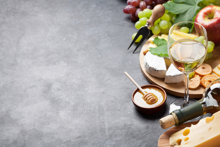 cheese plate: White wine, grape, bread, cheese plate and honey over stone table. View with copy space