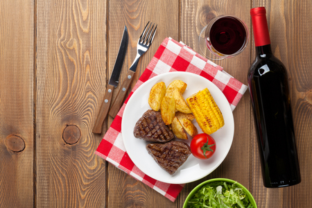 grilled potato: Steak with grilled potato, corn and red wine on wooden table with copy space
