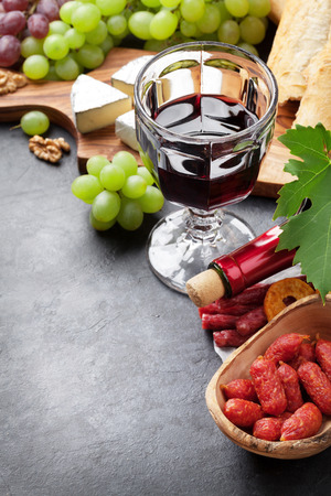 white cheese: Red wine grape, cheese, bread and sausages over stone table. View with copy space Stock Photo