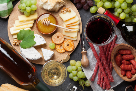 Red and white wine, grape, honey, cheese and sausages over stone table. Top view Stock Photo