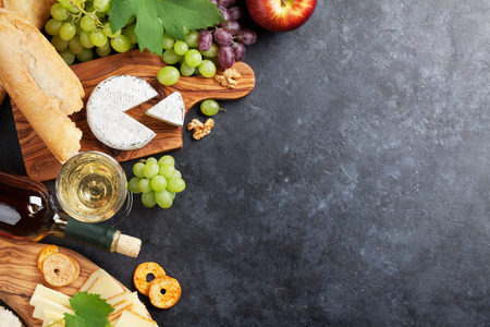 delicatessen: White wine, grape, bread and cheese on stone table. Top view with copy space Stock Photo