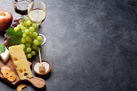 Vino tinto y blanco, uva, queso y miel en la mesa de piedra. Vista con espacio de copia