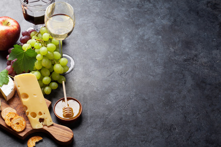 Red and white wine, grape, cheese and honey on stone table. View with copy space