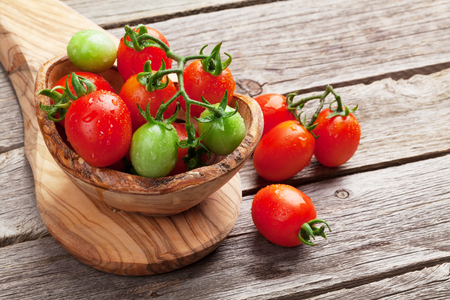 mesa de madera: Cherry tomatoes in bowl on wooden table