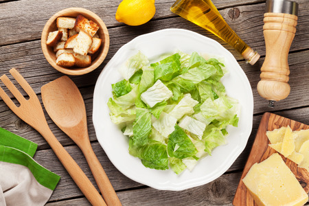 ensalada cesar: Fresh healthy caesar salad cooking on wooden table. Top view