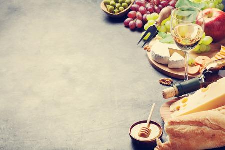 白ワイン、ブドウ、パン、チーズ プレート、石のテーブルの上に蜂蜜。コピー スペースを表示します。トーン