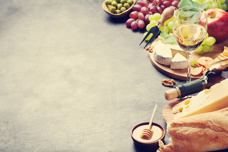 White wine, grape, bread, cheese plate and honey on stone table. View with copy space. Toned Stockfoto