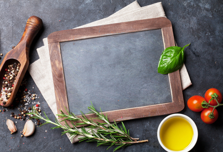 kitchen table top: Blank chalkboard for text, herbs and spices. Top view over stone table with copy space