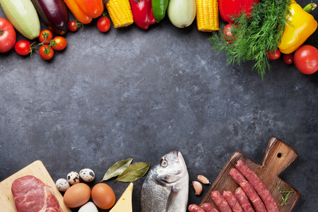 Vegetables, fish, meat and ingredients cooking. Tomatoes, eggplants, corn, beef, eggs, cheese. Top view with copy space on stone table Archivio Fotografico