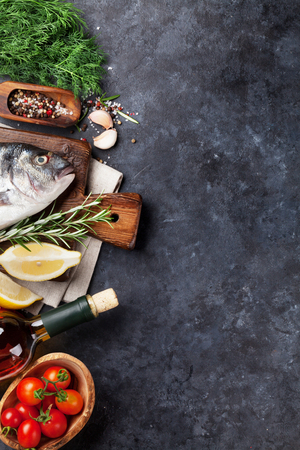 Raw fish cooking and ingredients. White wine, dorado, lemon, herbs and spices. Top view with copy space on stone table Stock Photo