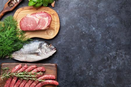 aves de corral: Salchichas, pescado, carne y los ingredientes para cocinar. Vista superior, con copia espacio en la mesa de piedra