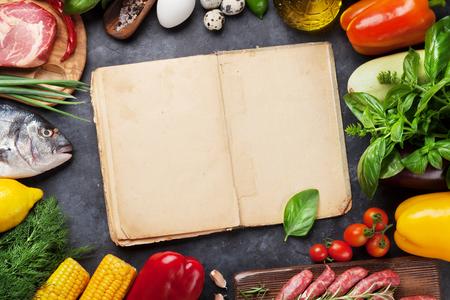 Groenten, vis, vlees en ingrediënten koken. Tomaten, aubergines, maïs, rundvlees, eieren. Bovenaanzicht met kookboek voor kopie ruimte op stenen tafel