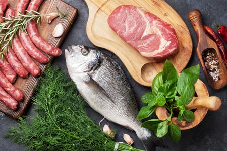 Saucisses, le poisson, la viande et les ingrédients de cuisson. Vue de dessus sur la table de pierre