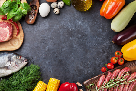 Vegetables, fish, meat and ingredients cooking. Tomatoes, eggplants, corn, beef, eggs. Top view with copy space on stone table Stockfoto