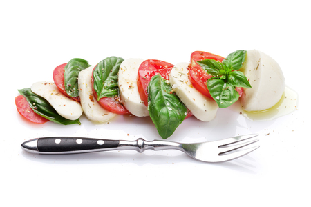 basil herb: Caprese salad and fork. Mozzarella cheese, tomatoes and basil herb leaves. Isolated on white background