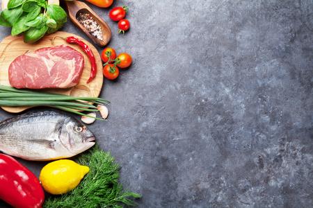 Groenten, vis, vlees en ingrediënten voor het koken. Tomaten, peper, maïs, rundvlees, eieren. Bovenaanzicht met kopie ruimte op stenen tafel