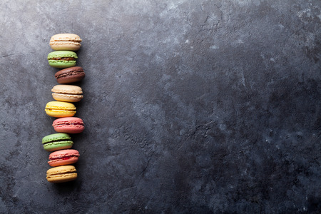 Colorful macaroons on stone table. Top view with copy space for text.