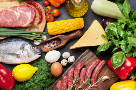 Vegetables, fish, meat and ingredients for cooking. Tomatoes, pepper, corn, beef, eggs. Top view on stone table Standard-Bild