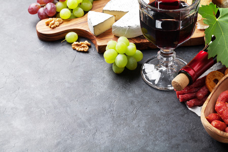 red grape: Red wine, grape, cheese, bread and sausages over stone table. View with copy space