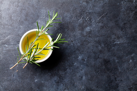 Rosemary and olive oil. Top view over stone table with copy space for recipe