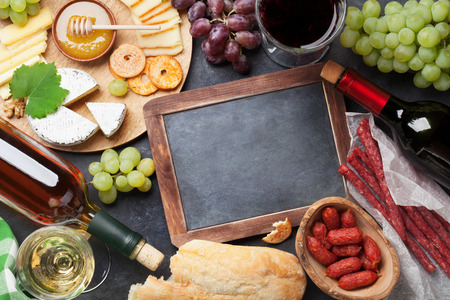 above: Red and white wine, grape, honey, cheese and sausages over stone table. Top view with blackboard for copy space