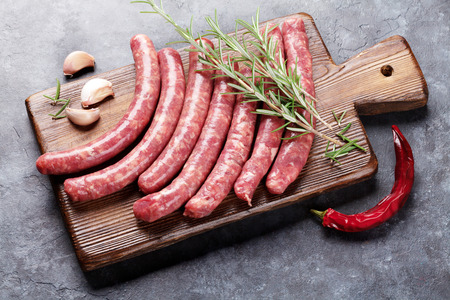 pork: Raw sausages and ingredients for cooking on stone table