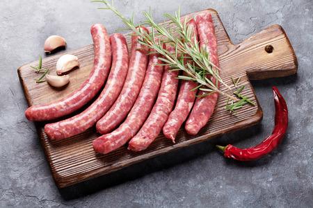 garlic: salchichas crudas e ingredientes para cocinar en la mesa de piedra