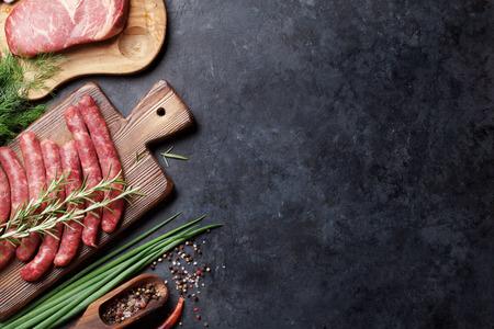 carne cruda: Embutidos, la carne y los ingredientes para cocinar. Vista superior de una mesa de piedra con copia espacio Foto de archivo
