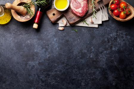 Bistecca di manzo grezza di cottura e gli ingredienti. pezzo di carne, vino rosso, erbe e spezie. Vista dall'alto con copia spazio sopra il tavolo in pietra
